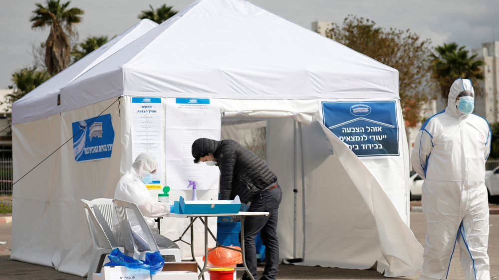 A paramedic in a protective suit helps a man as he prepares to vote in a special polling station set up by Israel's election committee so Israelis under home-quarantine, such as those