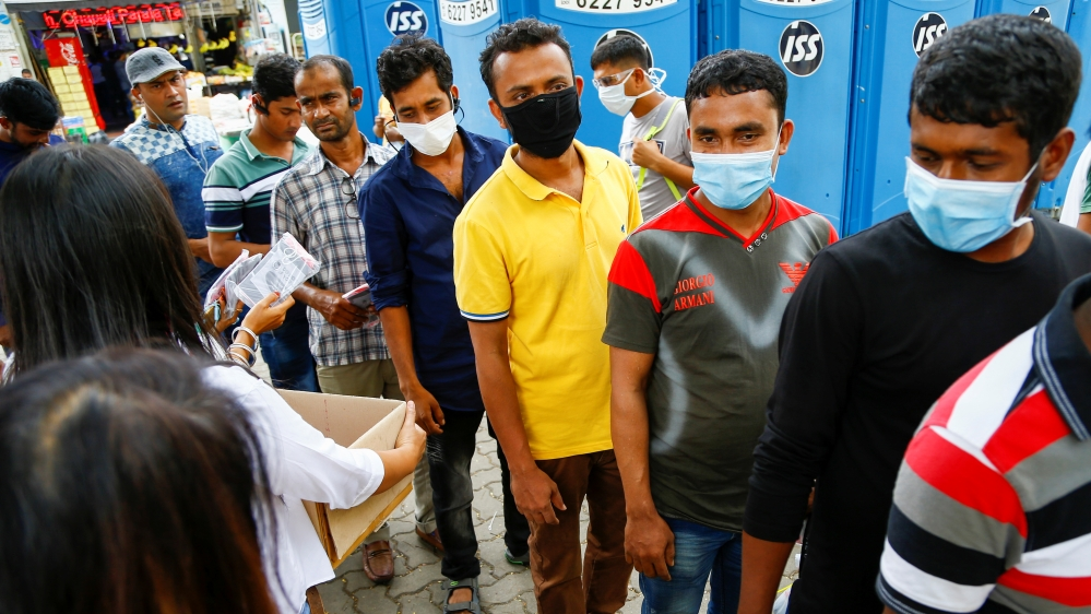 Migrant workers, mostly from Bangladesh, queue to collect free masks and get their temperatures taken in Singapore