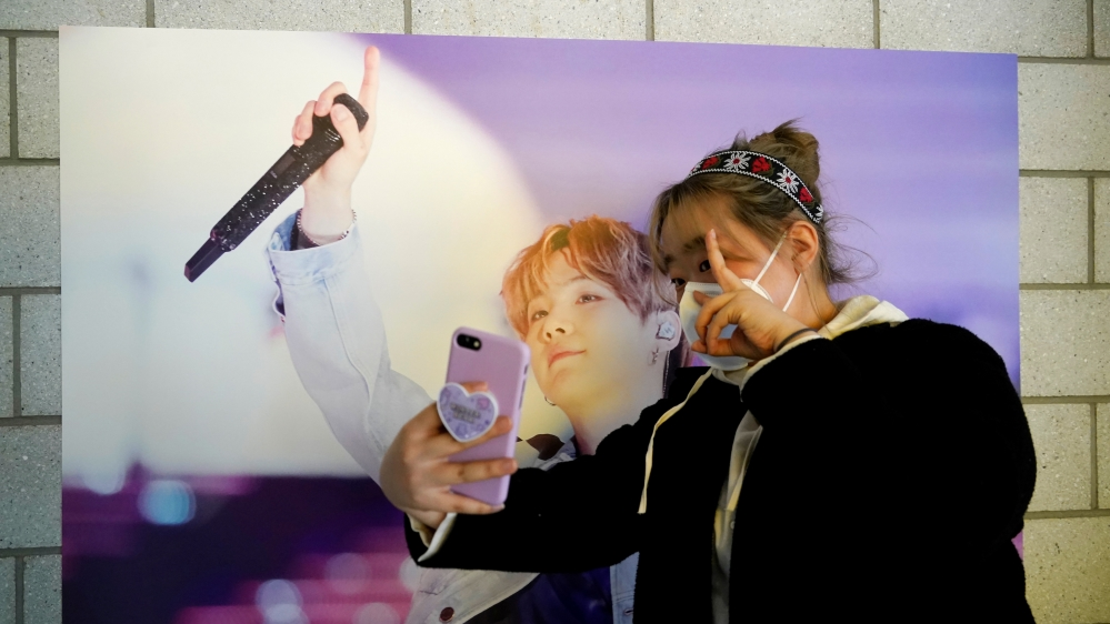 Im Yu-mi, fan of K-pop boy band BTS, takes a selfie at a cafe decorated with photos and merchandise of them, in Seoul, South Korea