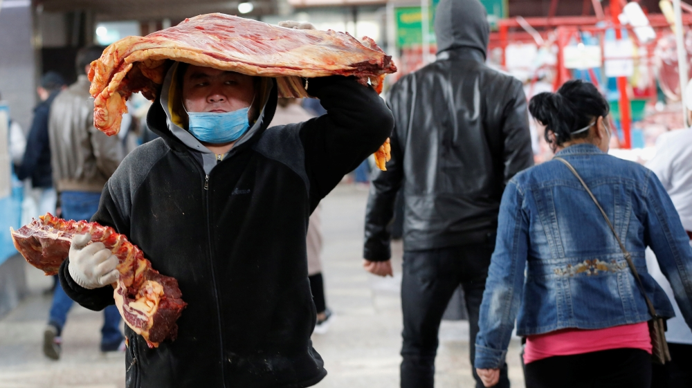 A worker wearing a protective face mask carries meat at a local food market in Almaty