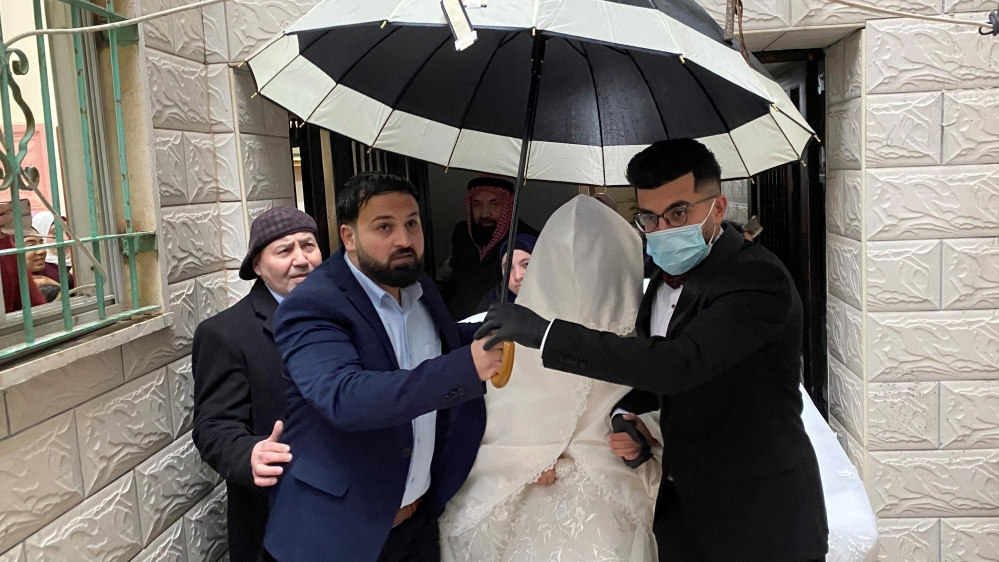 A Palestinian groom, wearing a mask as a preventive measure against the coronavirus disease, leaves with his bride her family house, on their wedding day in Beit Jala in the Israeli-occupied West Bank