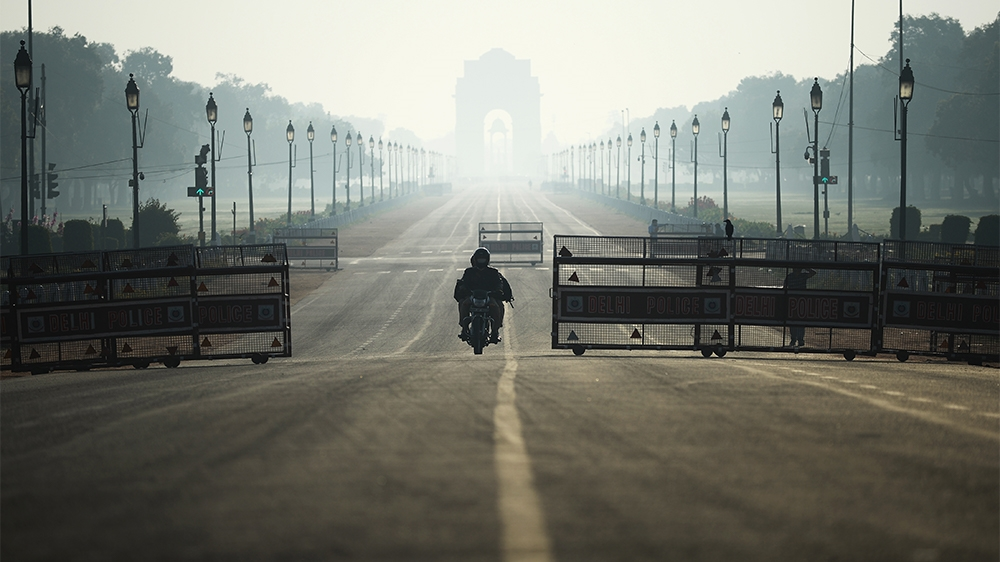 A motorist rides through deserted Rajpath road during a one-day Janata (civil) curfew imposed as a preventive measure against the COVID-19 coronavirus, in New Delhi on March 22, 2020. - Nearly one bil