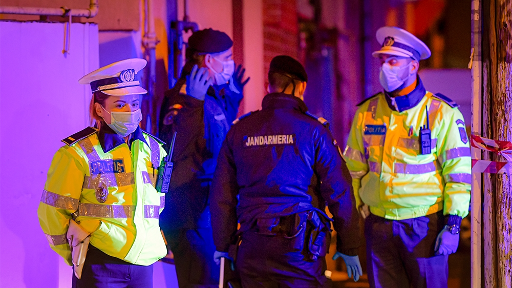 Illuminated by police car lights, a female police officer, left,  wearing a protective mask stands at a roadblock in the vicinity of one of the hospital where COVID-19 infected patients are under trea