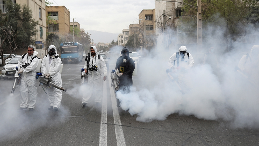 Members of firefighters wear protective face masks, amid fear of coronavirus disease (COVID-19), as they disinfect the streets, ahead of the Iranian New Year Nowruz, March 20, in Tehran, Iran March 18