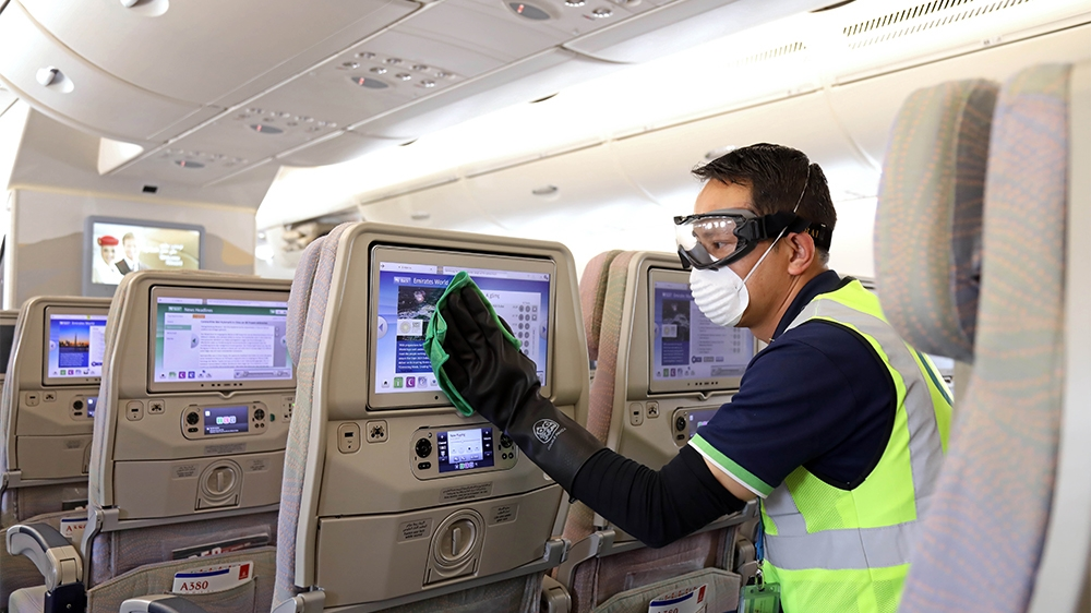 A handout image provided by Emirates airlines on March 8, 2020 in Dubai shows a member of the cleaning staff disinfecting seat screens aboard an Emirates Airbus A380-800 aircraft for sterilisation eff