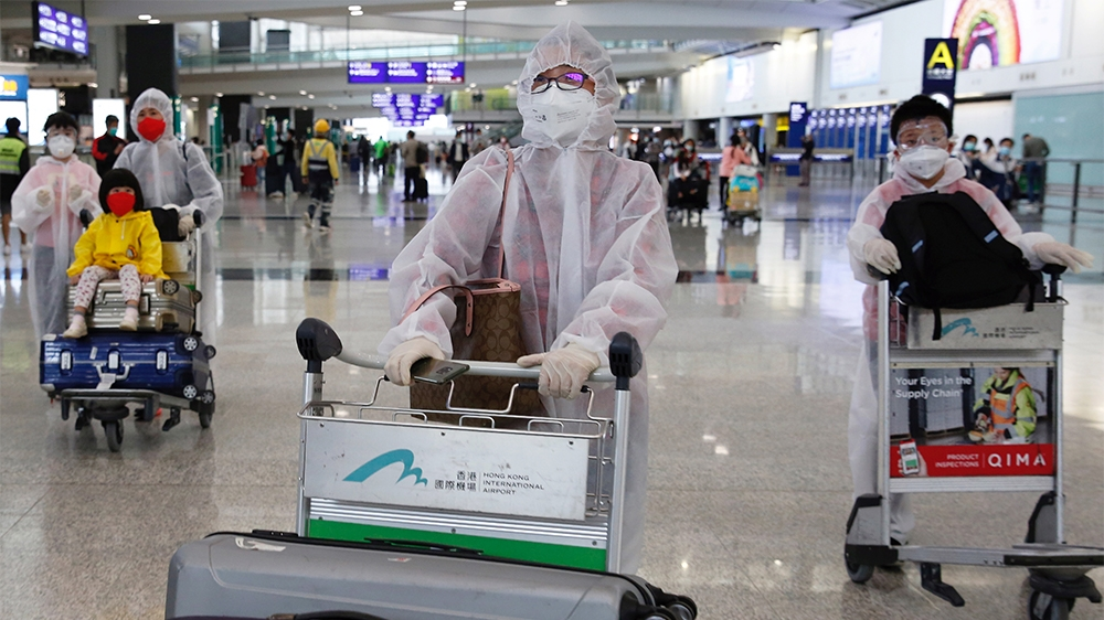 Passengers wear protective suits, amid the outbreak of coronavirus, at Hong Kong International Airport, Hong Kong, China March 17, 2020. REUTERS/Tyrone Siu
