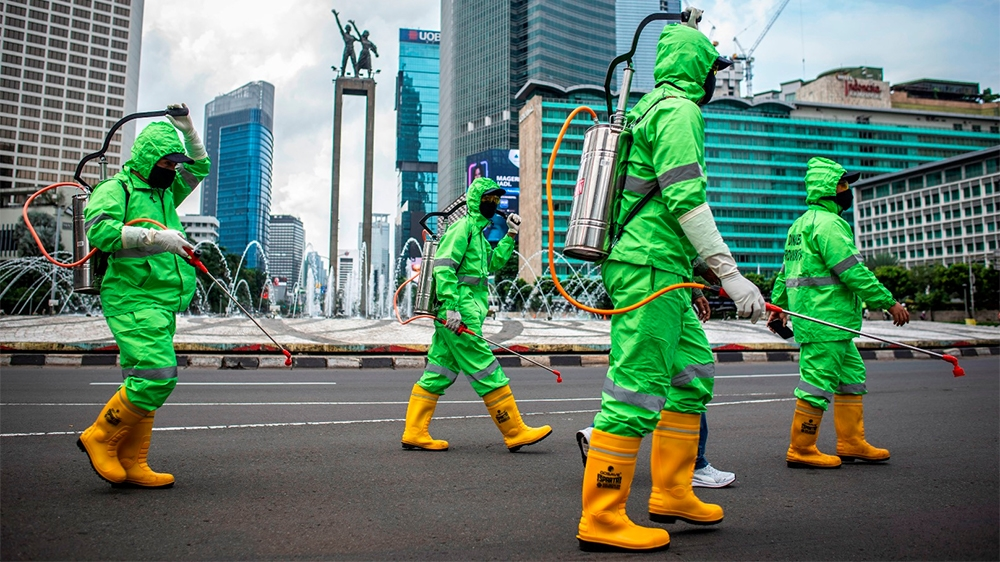 Workers walk in protective suits during an operation of spraying disinfectant to prevent the spread of coronavirus disease (COVID-19) in Jakarta, Indonesia March 22, 2020 in this photo taken by Antara