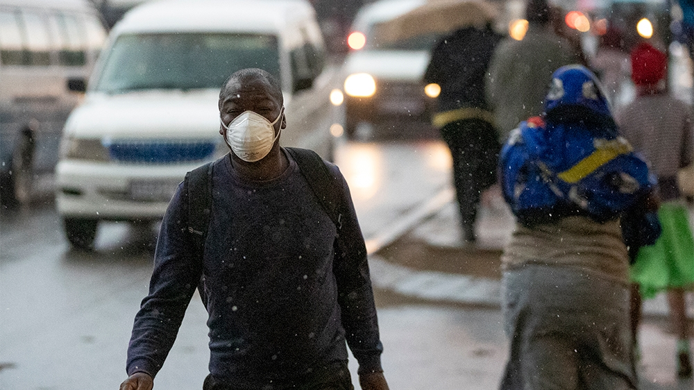 A man wearing a mask, walks on the street in Tembisa, east of Johannesburg, South Africa, Monday, March 23, 2020. South Africa, Africa's most industralized economy and a nation of 57 million people, w