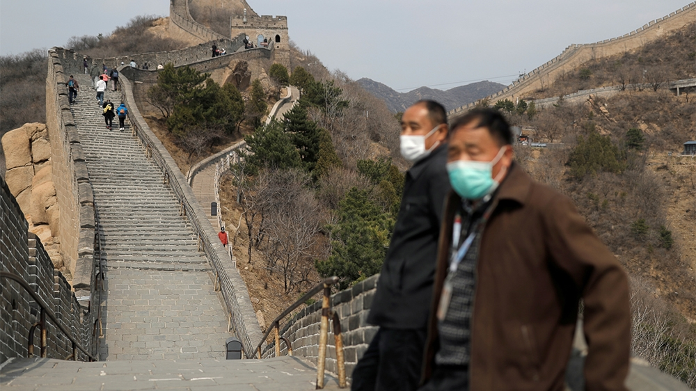 Men wearing protective masks stand as people hike along a section of the Great Wall in Badaling in Beijing, on its first day of re-opening after the scenic site
