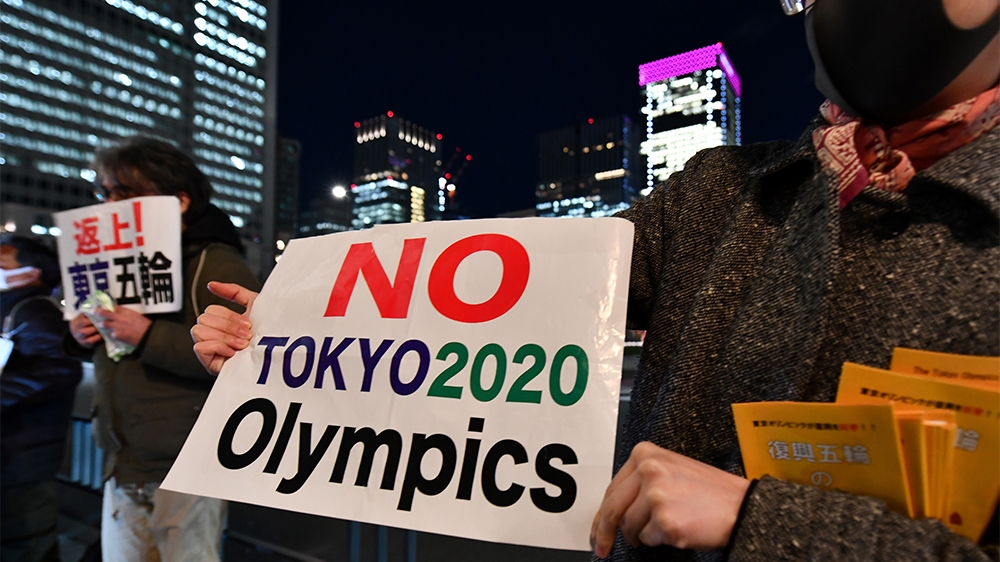 People opposed to the Tokyo 2020 Olympics display placards during a rally in front of Tokyo railway station on March 24, 2020. - The International Olympic Committee came under pressure to speed up its