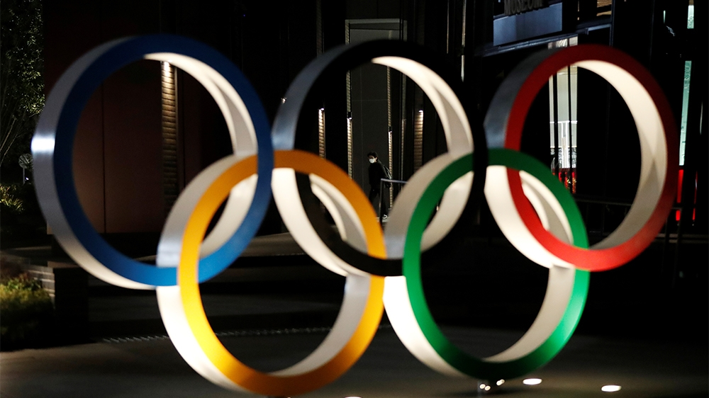 A passerby wearing a protective face mask, following an outbreak of the coronavirus disease (COVID-19), walks past the Olympic rings in front of the Japan Olympics Museum in Tokyo, Japan March 24, 202