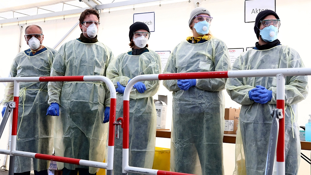 Medical employees wait to carry out tests at a coronavirus test center for public service employees, during a media presentation in Munich, Germany, Monday, March 23, 2020. For most people, the new co
