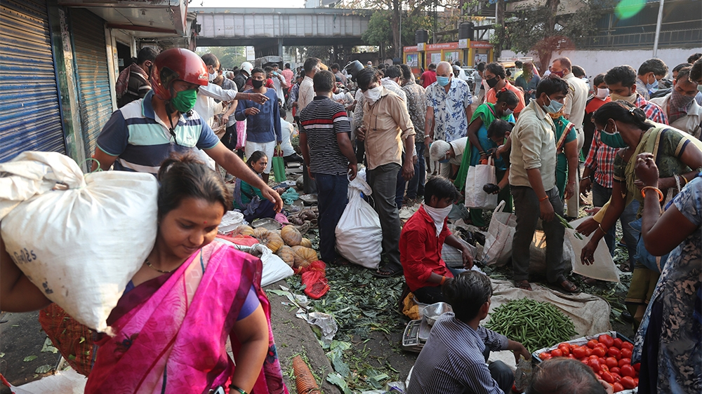 Indians crowd a vegetable market in Mumbai, India, Wednesday, March 25, 2020. The world's largest democracy went under the world's biggest lockdown Wednesday, with India's 1.3 billion people ordered t