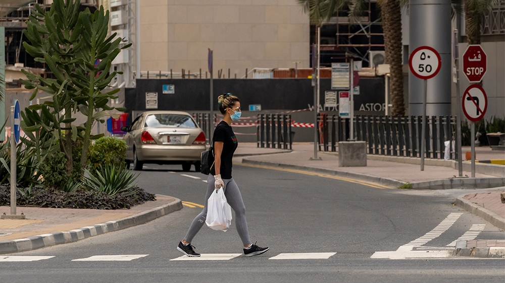 A woman wearing protective mask walks in West Bay area in Doha, Qatar, March 25, 2020. Qatar has imposed a series of measures to contain the coronavirus outbreak, including closing of parks and public