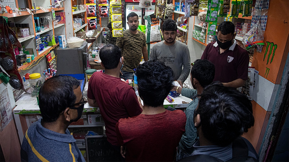 Indians buy essential commodities in a grocery shop in Gauhati, India, Tuesday, March 24, 2020. Indian Prime Minister Narendra Modi has decreed a 21-day lockdown across the nation of 1.3 billion peopl