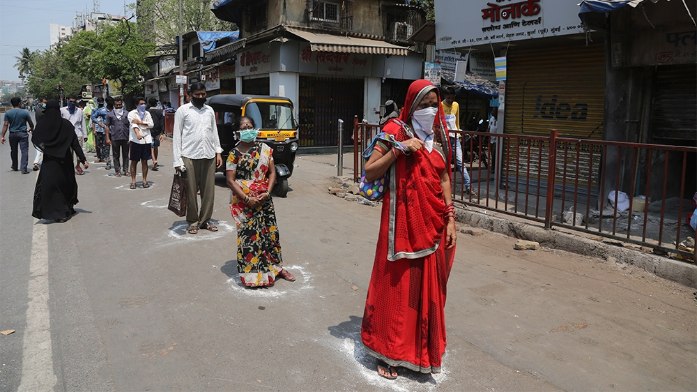 Indians stand in marked positions to buy essential commodities from a grocery store in Mumbai, India, Wednesday, March 25, 2020.The world's largest democracy went under the world's biggest lockdown We