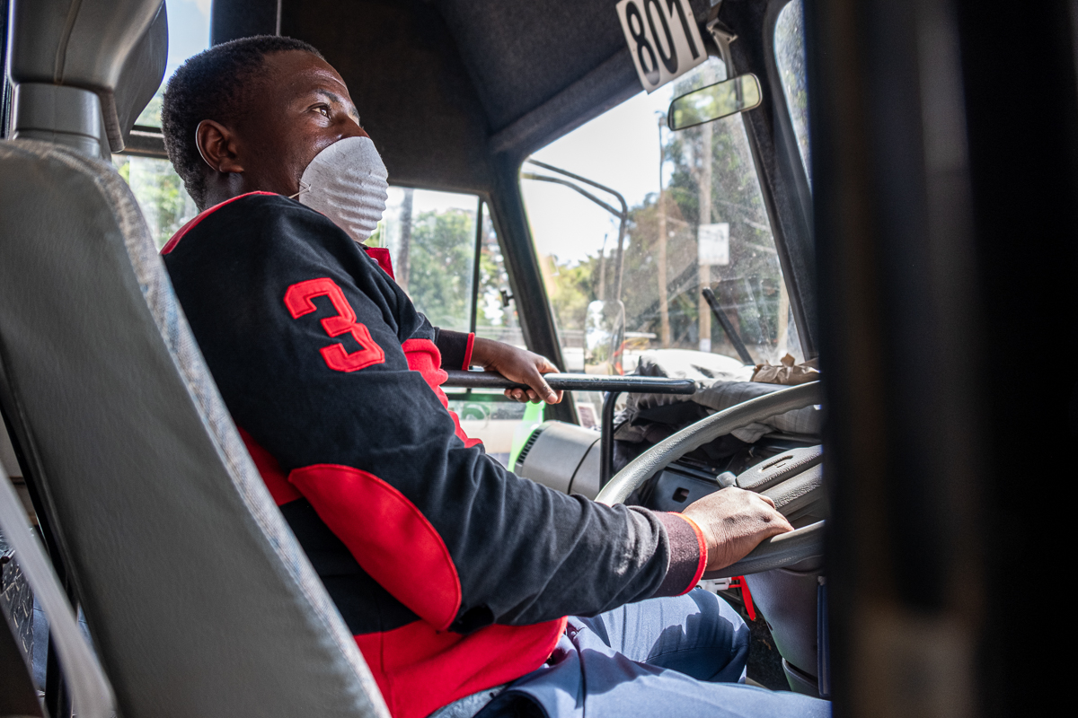 Matatu driver Nicholas Peter wears a face mask behind the wheel. [Joost Bastmeijer/Al Jazeera]