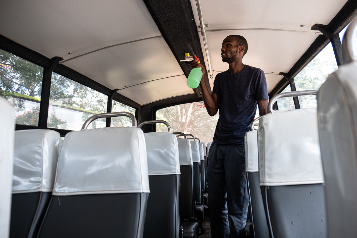 Edward, who works as a matatu tout, cleans the seats of the bus when there are no passengers in between shifts. 'We are cleaning the bus multiple times a day,' he says. 'We disinfect the seats and the metal bar that people hold when we are on the road.' [Joost Bastmeijer/Al Jazeera]