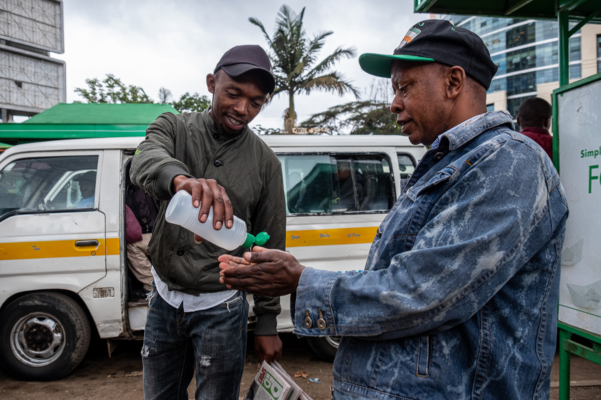 Before people can enter the matatus, their hands are disinfected by matatu touts like Lucky John, left. 'This is an advanced hand-sanitiser,' he says. 'Many people will not be able to afford to go to the hospital. And if you can't seek medical attention, you will die. So no one here needs to get that coronavirus, we take our own precautions. We don't want to die, everybody here loves their life. So we are taking every step, every measure seriously.' [Joost Bastmeijer/Al Jazeera]
