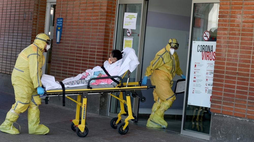 Des ambulanciers en tenue de protection complète arrivent avec un patient à l'hôpital Severo Ochoa pendant l'épidémie de maladie à coronavirus (COVID-19) à Leganes, en Espagne, le 26 mars 2020. REUTERS / Susana Vera