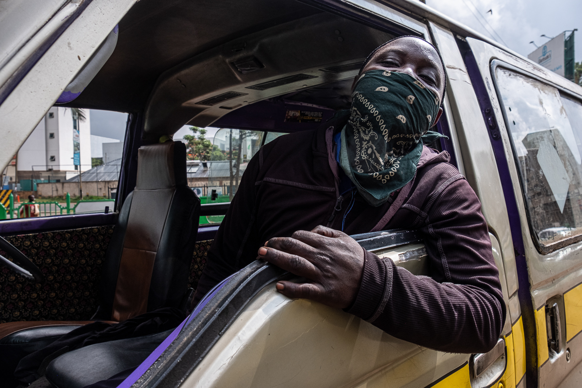 A matatu passenger wears a bandana in an attempt to protect him from the coronavirus. [Joost Bastmeijer/Al Jazeera]