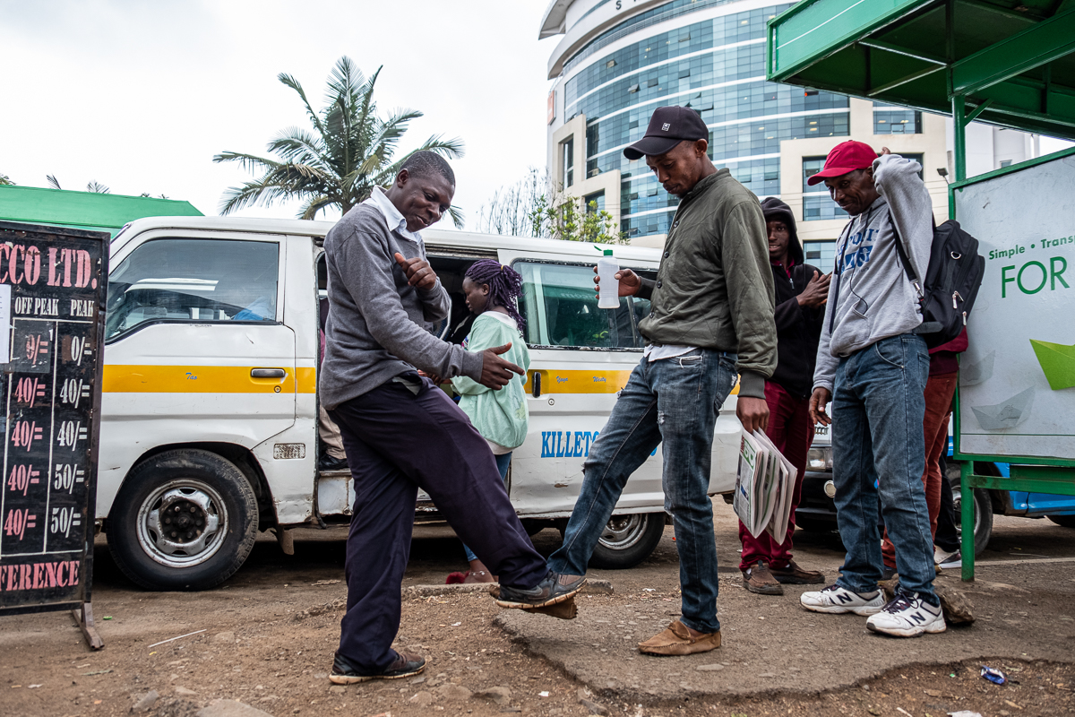 Lucky John greets a friend with a 'foot bump'. 'We now greet like this, with our feet and our elbow. Sometimes even with our hips!' said Lucky. President Uhuru Kenyatta said in a statement that 'social distancing is now our new norm, it is our new way of life.' [Joost Bastmeijer/Al Jazeera]