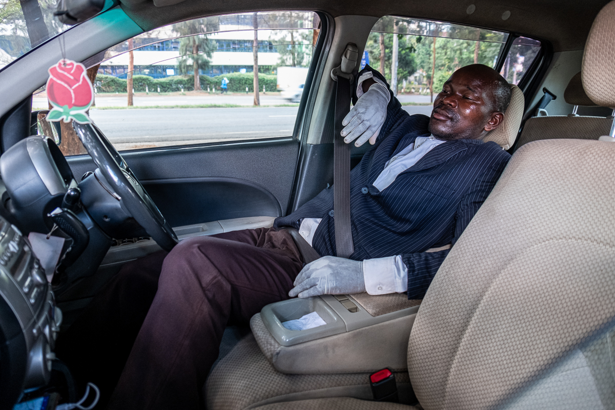 Close to the bus station, an Uber driver in Nairobi relaxes in between rides, wearing protective gloves. [Joost Bastmeijer/Al Jazeera]