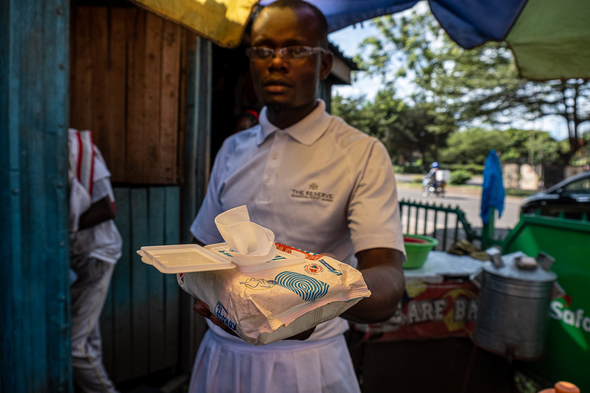 The owner of a roadside restaurant at Westlands Terminal offers a disinfectant towel upon entry. [Joost Bastmeijer/Al Jazeera]
