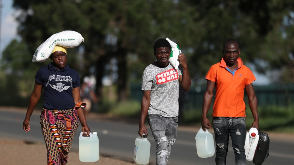 People carry bags of maize and paraffin as they return from a store ahead of a nationwide lockdown, in Johannesburg