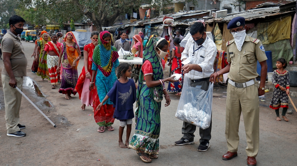 Slum dwellers receive free food packets during a 21-day nationwide lockdown to limit the spread of the coronavirus disease (COVID-19), in Ahmedabad