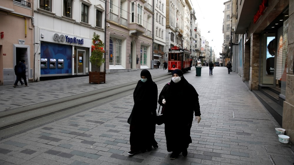 Women wearing protective face masks and gloves are seen as the spread of the coronavirus disease (COVID-19) continues, Istanbul, Turkey, March 26, 2020. REUTERS/Umit Bektas