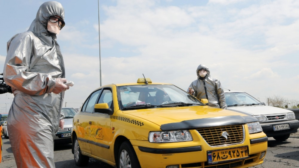 Coronavirus precautions in Iran- - TEHRAN, IRAN - MARCH 26: Health officials check body temperature of drivers and passengers at the entrance
