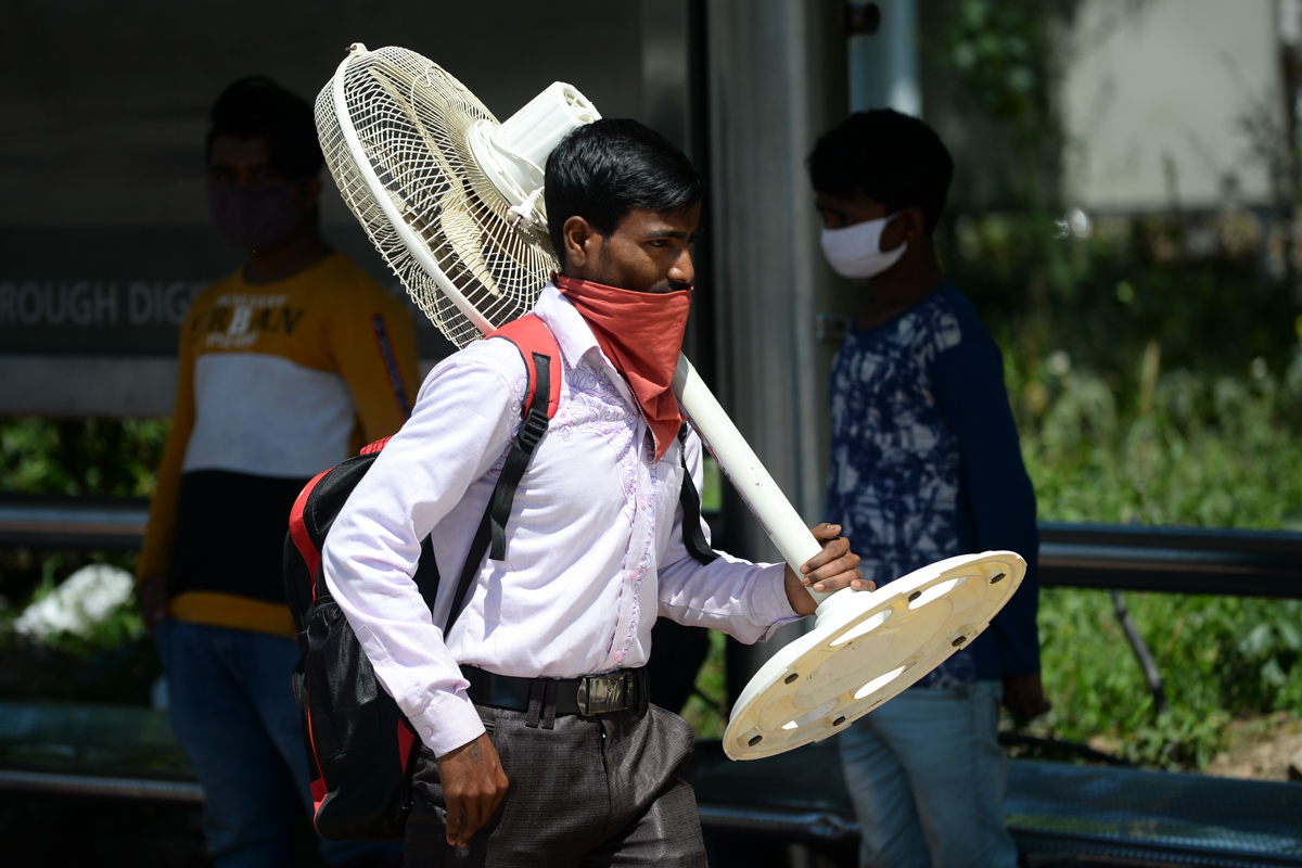 A migrant worker carrying a fan walks along a road as he leaves India's capital for his home during a government-imposed nationwide lockdown. [Sajjad Hussain/AFP]