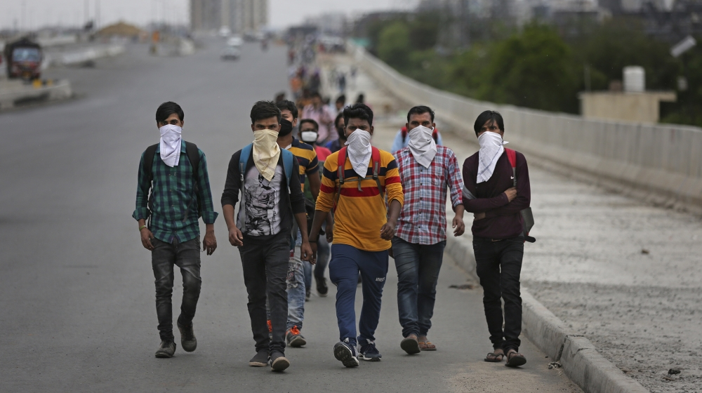A group of Indian daily wage laborers walk along an expressway hoping to reach their homes, hundreds of kilometers away, as the city comes under lockdown in Ghaziabad, on the outskirts of New Delhi, I