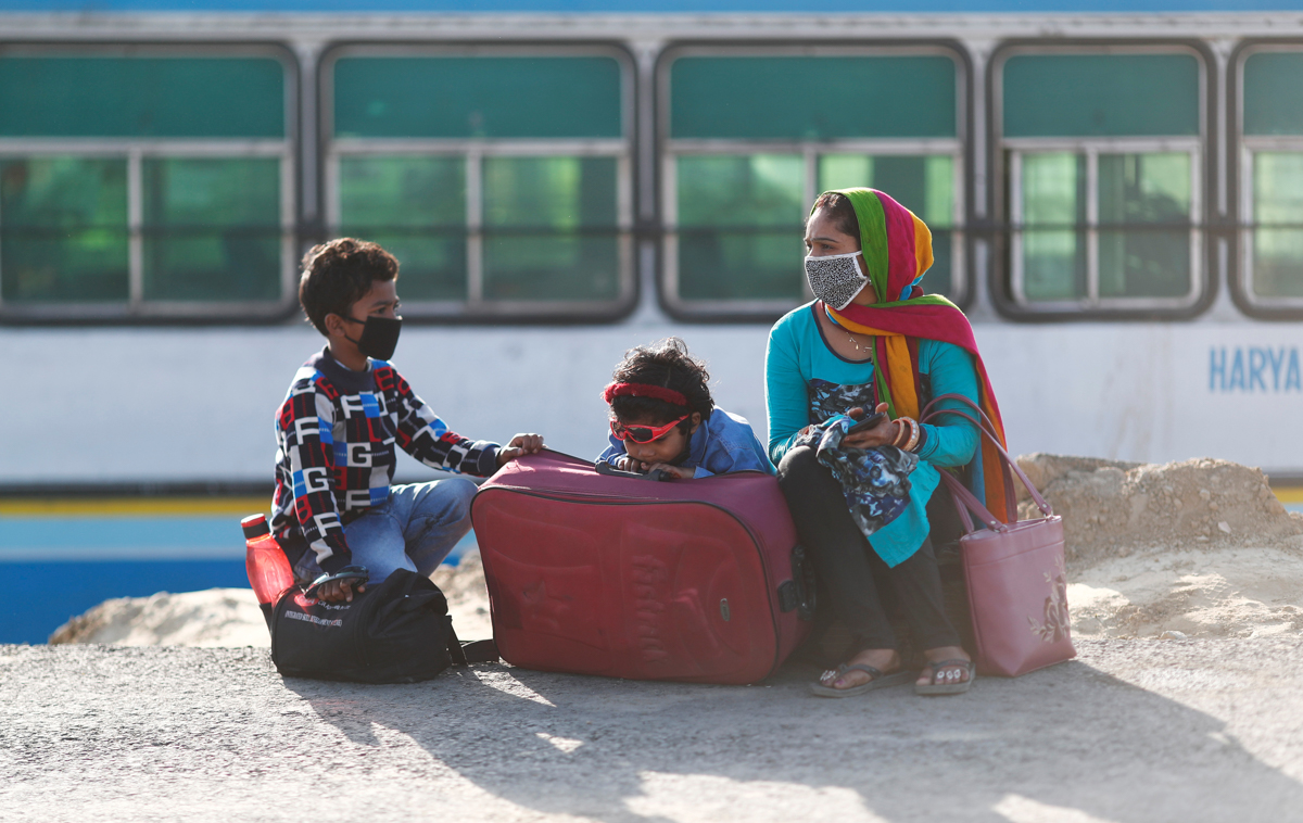 A family of a migrant worker sits along a highway as they wait for a bus to return to their village. [Adnan Abidi/Reuters]