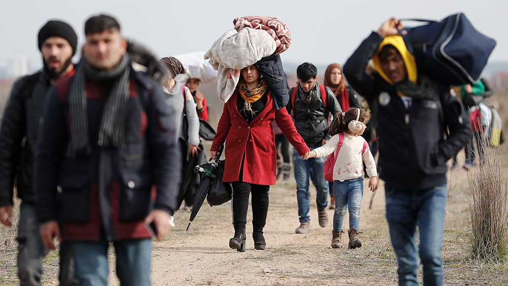 Refugees and migrants walk in a dirty road heading to the Turkish-Greek border and trying to enter Europe, in Edirne, Turkey, 01 March 2020. The Turkish government announced its decision to no longer