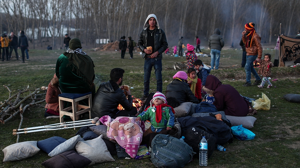 epa08262947 A group of migrants rests near Meric (Evros) River as they wait to cross to reach Greece at the Turkish-Greek border, in Edirne, Turkey, 01 March 2020. Thousands of refugees and migrants a