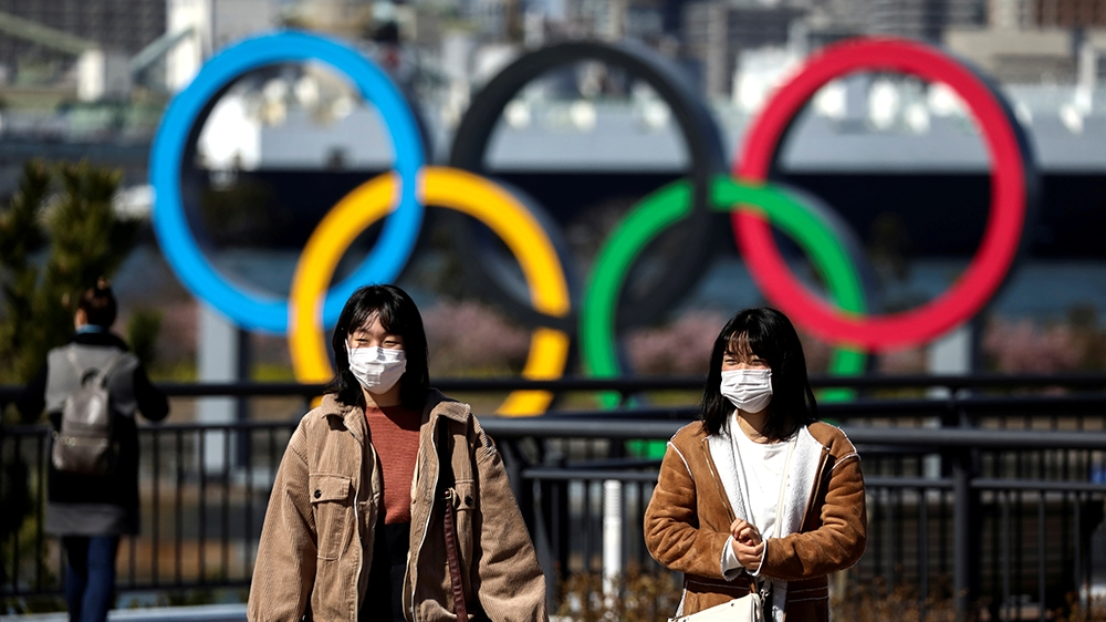 FILE PHOTO: People wearing protective face masks, following an outbreak of the coronavirus, are seen in front of the Giant Olympic rings at the waterfront area at Odaiba Marine Park in Tokyo, Japan, F