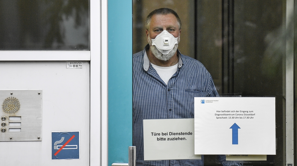 An employee with face mask and gloves waits behind the door of the corona diagnostic center in Duesseldorf, Germany, Monday, March 2, 2020 for the next patient. Germany faces several people infected w