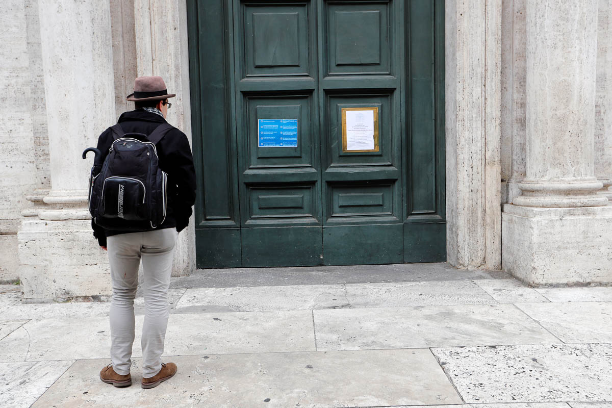 A man looks at the closed doors of the church of St Louis of the French in the heart of Rome. It was closed as a precautionary measure after a priest came down with coronavirus. [Remo Casilli/Reuters]