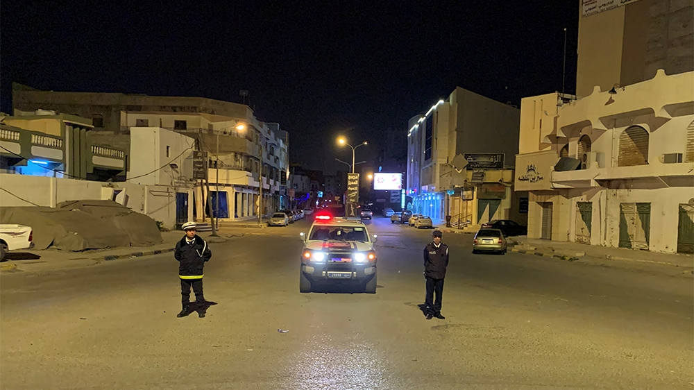 Police officers stand in the middle of the road during a curfew, imposed as part of precautionary measures against coronavirus disease (COVID-19), in Misrata, Libya March 22, 2020. Picture taken March