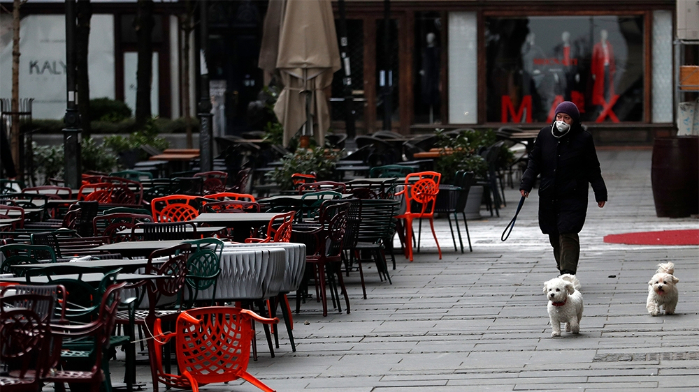 A woman walks with dogs in a deserted street amid the coronavirus outbreak in downtown Belgrade, Serbia, Thursday, March 26, 2020.   (AP Photo/Darko Vojinovic)