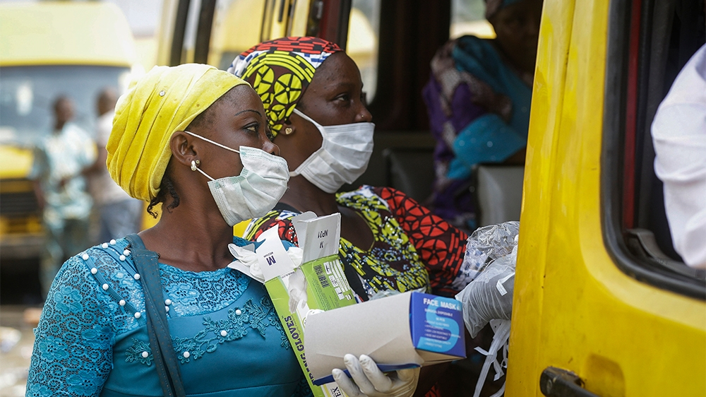 Women sell face masks and gloves, to prevent the spread of the new coronavirus, to passengers at a public minibus station in Lagos, Nigeria Friday, March 27, 2020. The new coronavirus causes mild or m