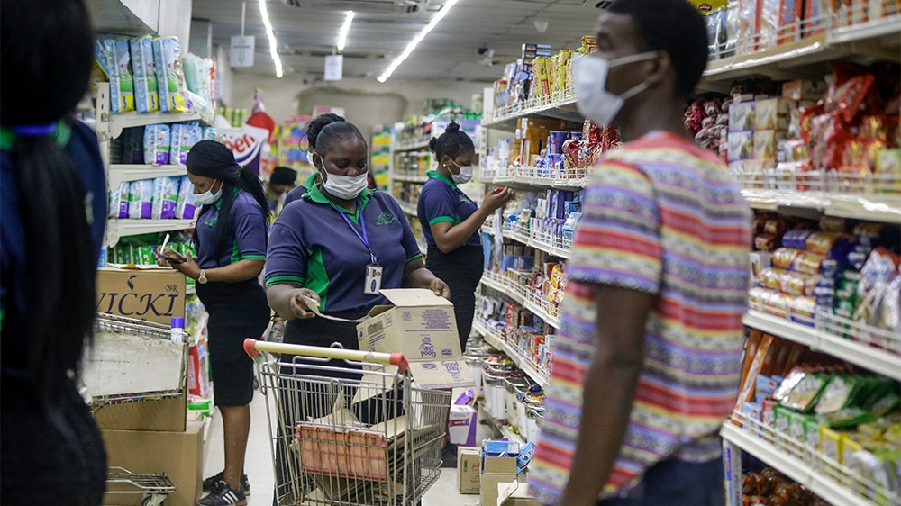Shop assistants wearing face masks to prevent against the spread of the new coronavirus take stock in a supermarket in Lagos, Nigeria Friday, March 27, 2020. The new coronavirus causes mild or moderat