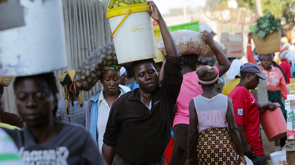 Women carry  various foodstuffs at a local market in  Harare, Zimbabwe, Friday,March, 27, 2020.Zimbabwes public hospital doctors are on strike over what they called a lack of adequate protective  gear