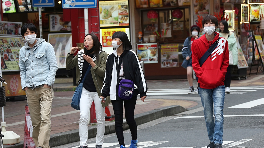 People wearing face masks to protect against the spread of the new coronavirus walk on a Yokohama China Town near Tokyo, Tuesday, March 31, 2020. (AP Photo/Koji Sasahara)
