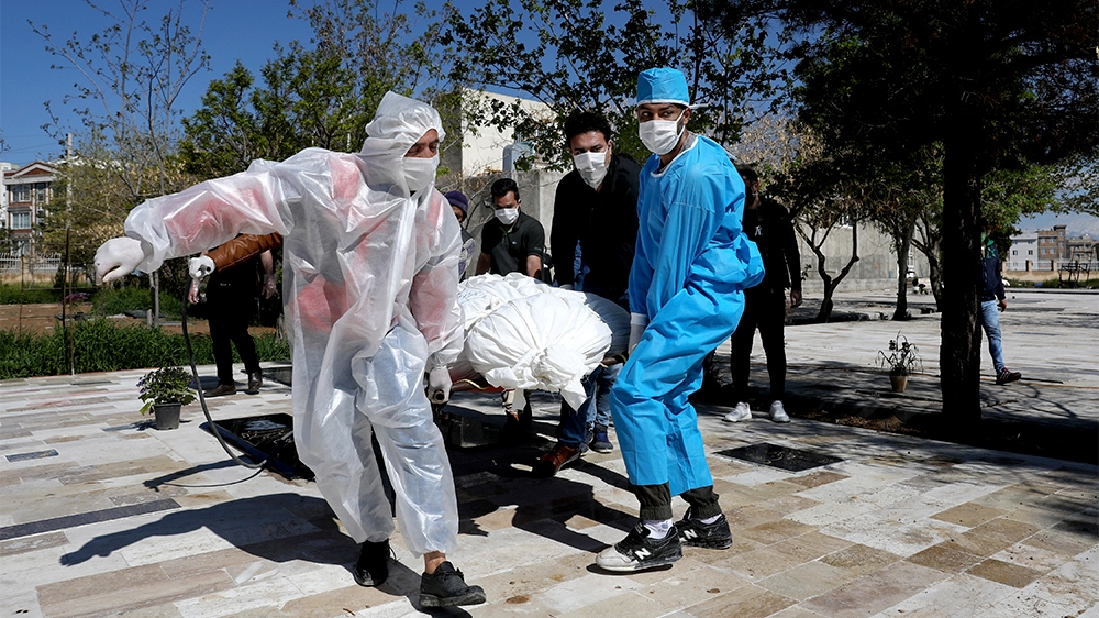 People wearing protective clothing carry the body of a victim who died after being infected with the new coronavirus at a cemetery just outside Tehran, Iran, Monday, March 30, 2020. The new coronaviru