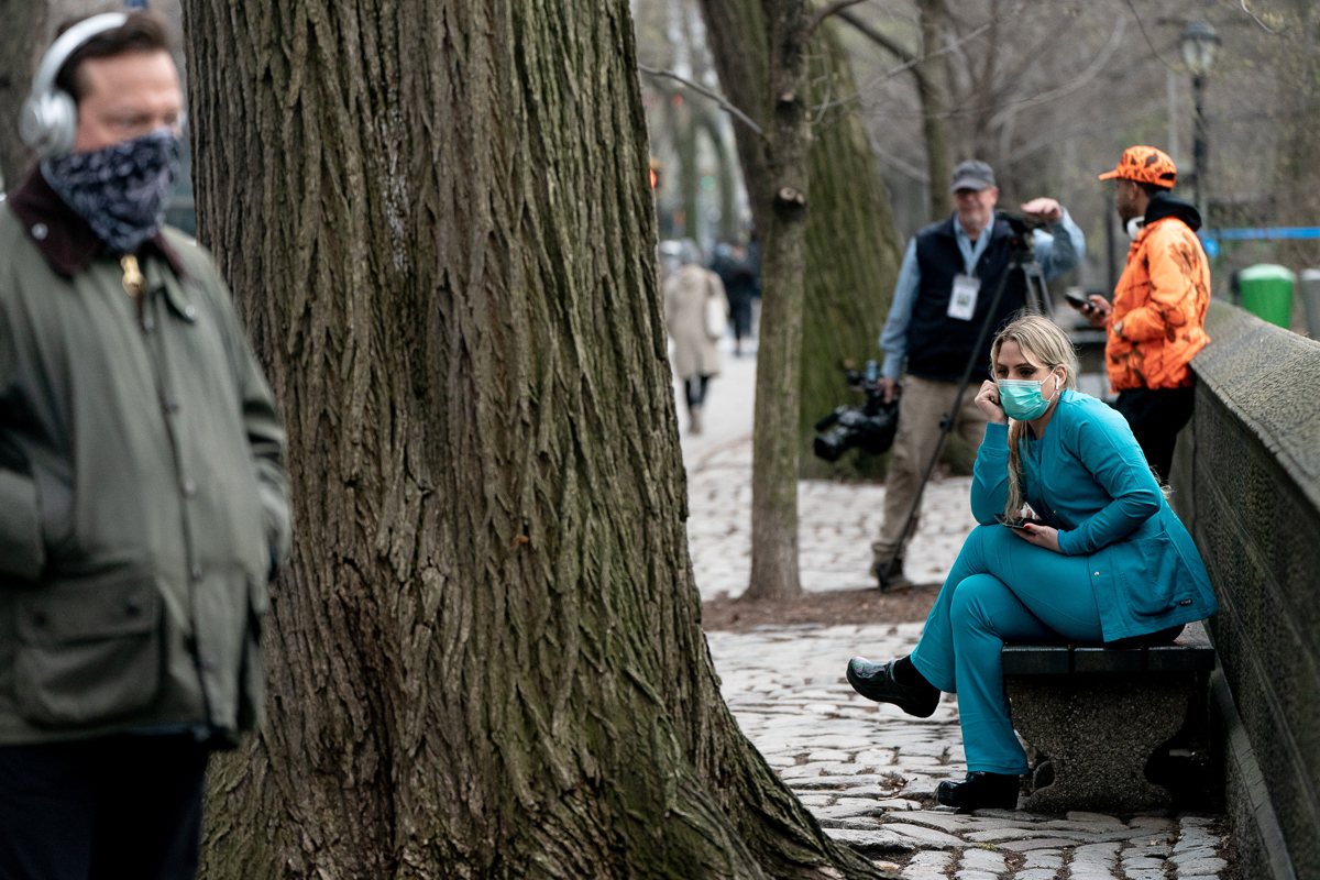 A healthcare worker sits on a bench near Central Park, Manhattan. [Jeenah Moon/Reuters]