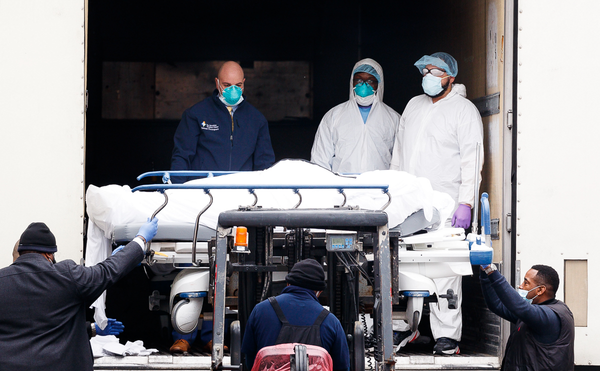 epa08333051 Medical professionals and hospital employees transfer a body on a hospital gurney into temporary storage in a mobile morgue, being used due to lack of space at the hospital, outside of the
