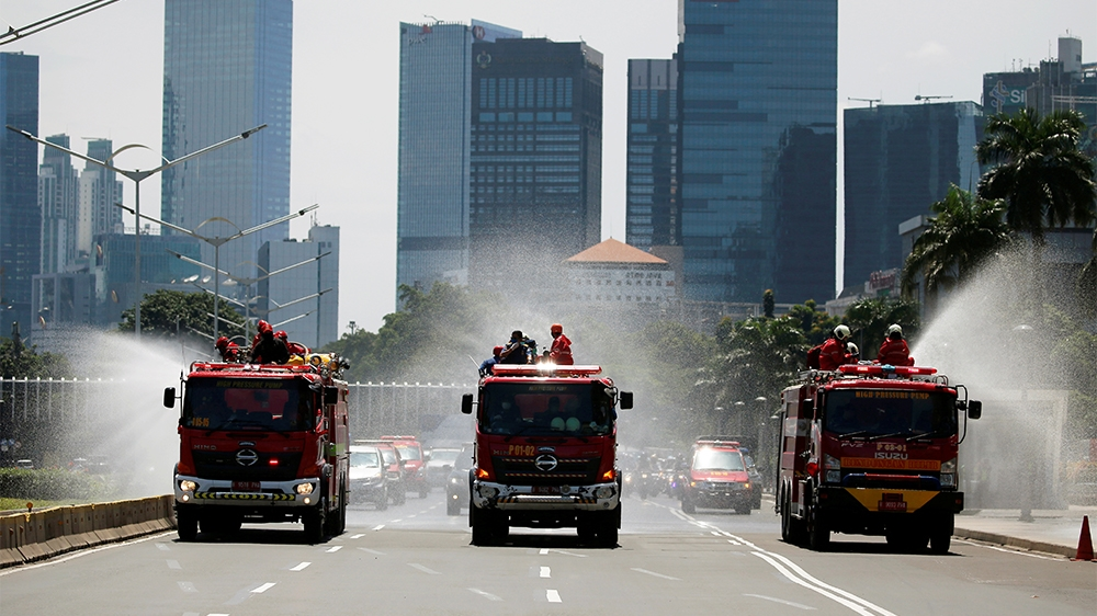 Firefighters spray disinfectant using high pressure pump trucks to prevent the spread of coronavirus disease (COVID-19), on the main road in Jakarta, Indonesia, March 31, 2020. REUTERS/Willy Kurniawan